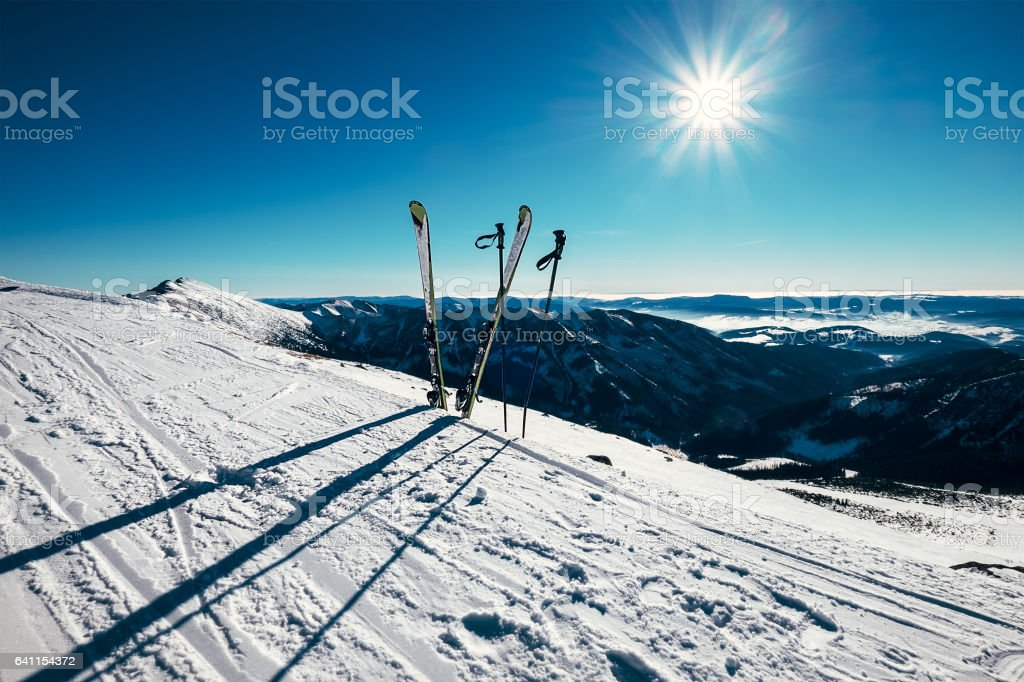 Skis are in deep snow on the ski track in sunny bright light stock photo