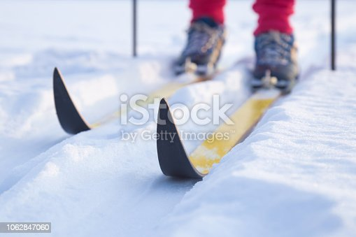 Skis on track in the fresh, white snow in winter day. Classic cross country skiing. Active lifestyle. Enjoying sport. Closeup.