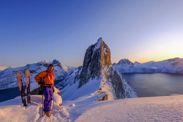 Skitouring man standing at the ridge in front of the iconic Segla mountain, view of the ocean fjords, Fjordgard, Norway stock photo