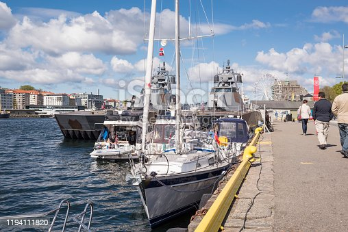 Bergen, Norway - May 14, 2016: The harbor of the City of Bergen on the west coast of Norway on a sunny day at noon in spring. The sky is blue with white puffy cumulus clouds. In the foreground are a sail ship (yacht)  and three motor boats. In the background are two military (war) ships, Storm and Steil, belonging to the Royal Norwegian Navy. They are superfast, catamaran, stealth missile corvettes of the Skjold (Shield) class. The Skjold-class corvettes are currently the fastest armed craft in the world with 60 knots (110 km/h). To ensure stealth capabilities, anechoic coatings of radar absorbent materials have been used over large areas of the ship. Corvette is traditionally the smallest class of vessel considered to be a proper (or