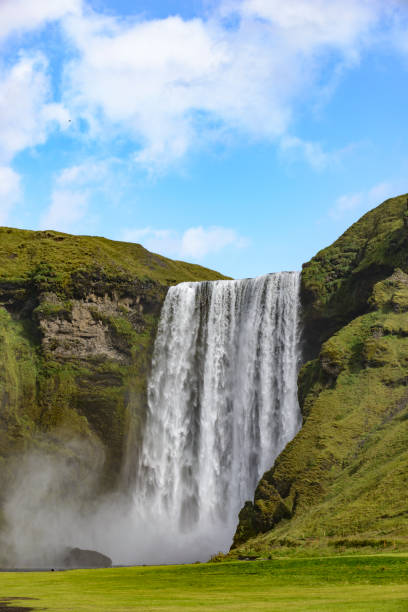 Skogafoss waterfall in Iceland on a summer's day with a blue sky above stock photo