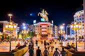 Skopje, Republic of Macedonia - July 19, 2016:   view showing Skopje City Center , buildings and the statue of Alexander the Great, fountain, street lights and people walking on the street can be seen on the background at night