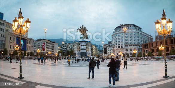 Skopje, Macedonia, October 2016: City center of Skopje, capital of North Macedonia. Pedestrians passing by. High monument of The Alexander The Great and surrounding fountain can be seen in the shot. Evening shot.