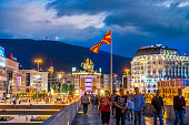 Skopje, Republic of Macedonia - July 19, 2016:   view showing Skopje Macedonia Square, hotel buildings, statues, stone bridge, flag, mountains, trees and people walking on the bridge can be seen on the background at night