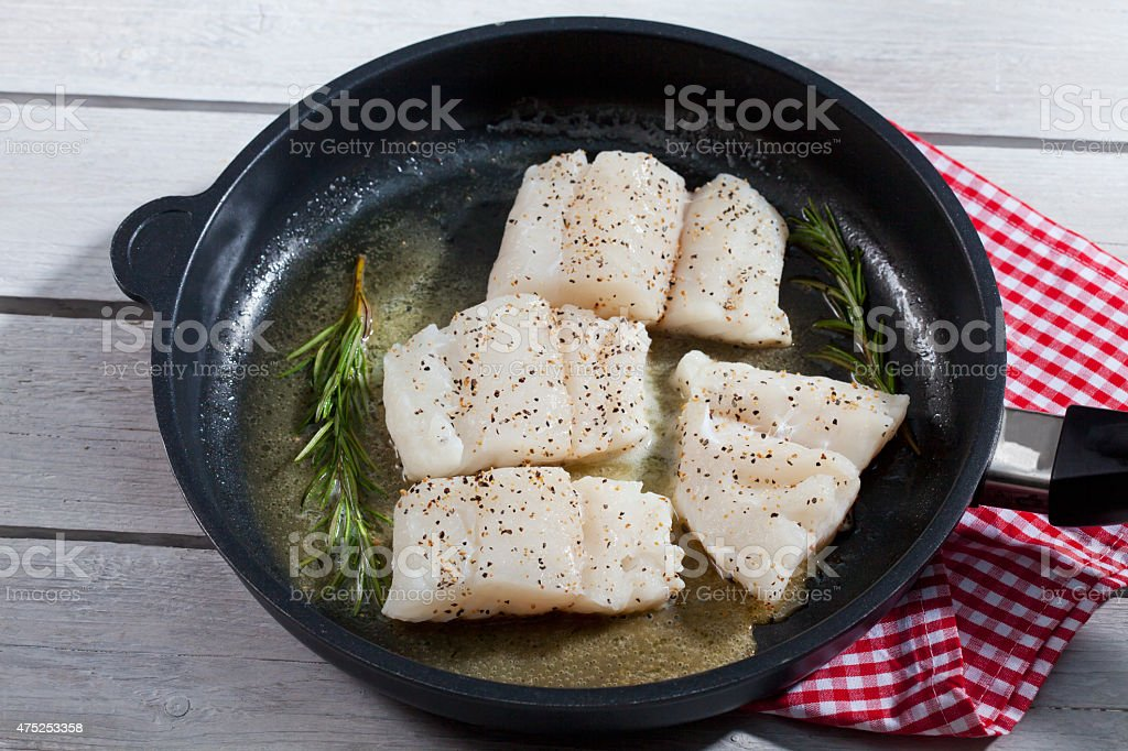 Skrei cod filet in pan with rosmary stock photo