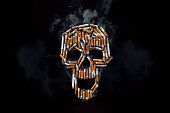 istock Skull from cigarettes, butts, on a black background. Creative background. The concept of smoking kills, nicatine poisons, cancer from smoking, stop smoking. Copy space. 1075915032