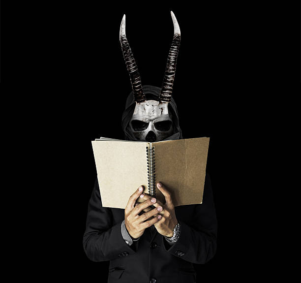 skull guy with horns in black suit reading notebook - horror bücher stock-fotos und bilder