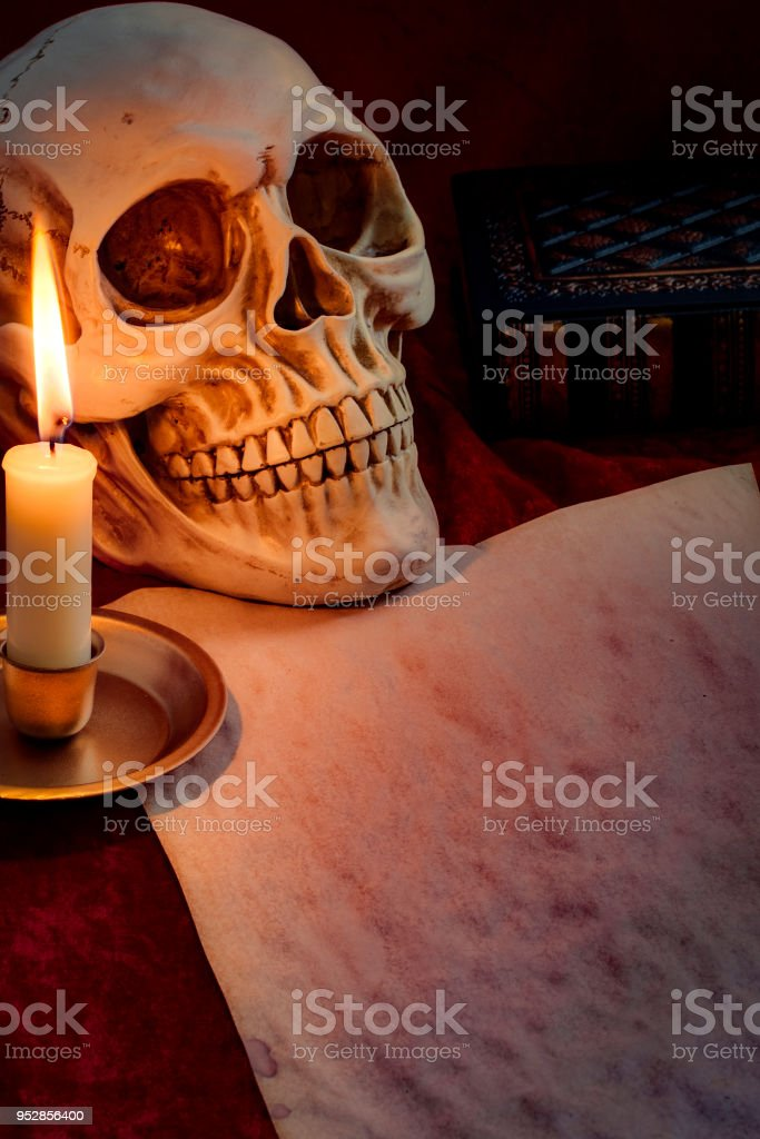 Skull, lit candle and aed paepe with copyspace stock photo