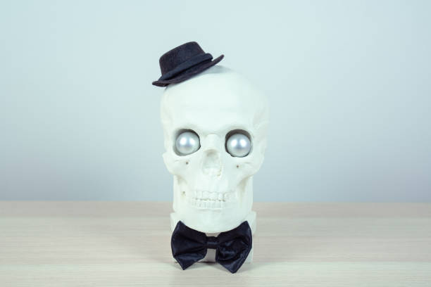 skull sculpture with black hat and a black  bow tie.  holiday background concept. Free space for design. stock photo