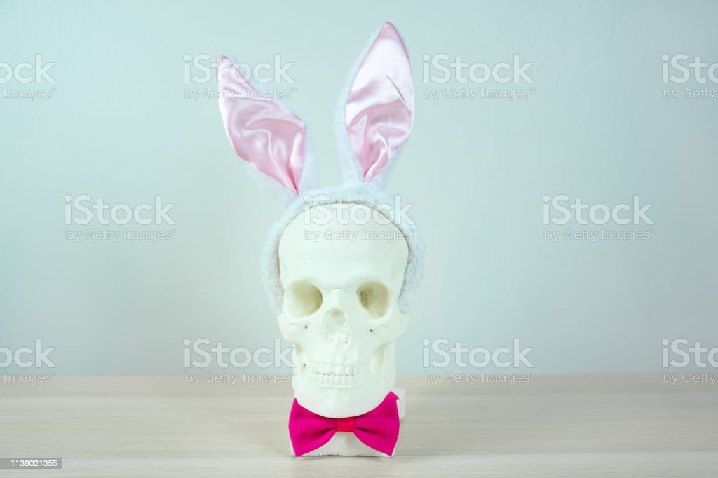 skull sculpture with bunny ear headbands and a pink bow tie. symbol...