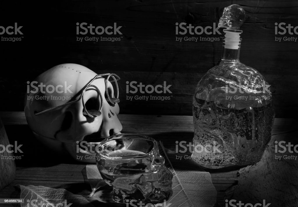 Skull shaped ashtray with glasses and bottles and glasses, skulls , strawberry juice in black adn white stock photo