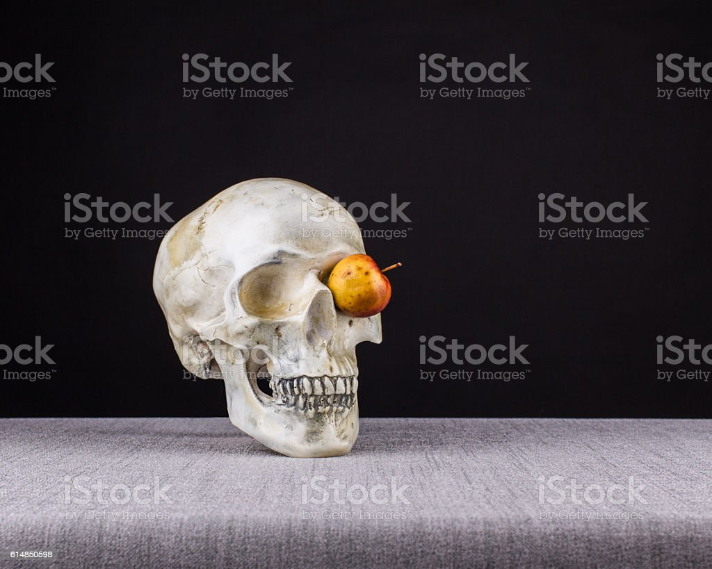 Skull smelling and watching  with one eyes of apple stock photo