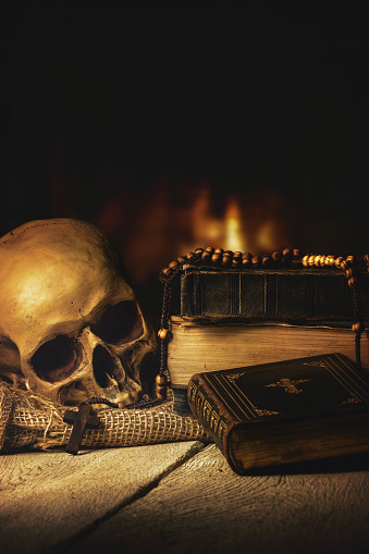 Skull With Rosary And Bible In Front Of A Fireplace Stock Photo - Download Image Now