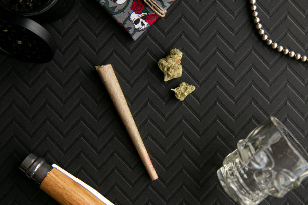 Skulls and Roses Red and Black Cannabis Scene with Marijuana, Pre-roll, Weed Grinder and Pouch, on Chevron Black Background - Top Down stock photo