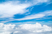 White clouds and blue sky view from airplane window. Beautiful cloudscape from sky  aerial view. Beauty of nature view from above the sky and clouds. Sunlight in the sky shines on clouds.