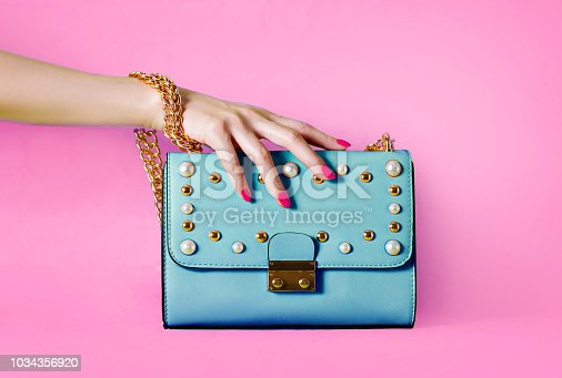 istock Sky blue handbag purse and beautiful woman hand with red manicure isolated on pink background. 1034356920