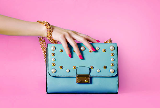 Sky blue handbag purse and beautiful woman hand with red manicure isolated on pink background. Beautiful woman hand with red manicure is holding the purse. bag stock pictures, royalty-free photos & images