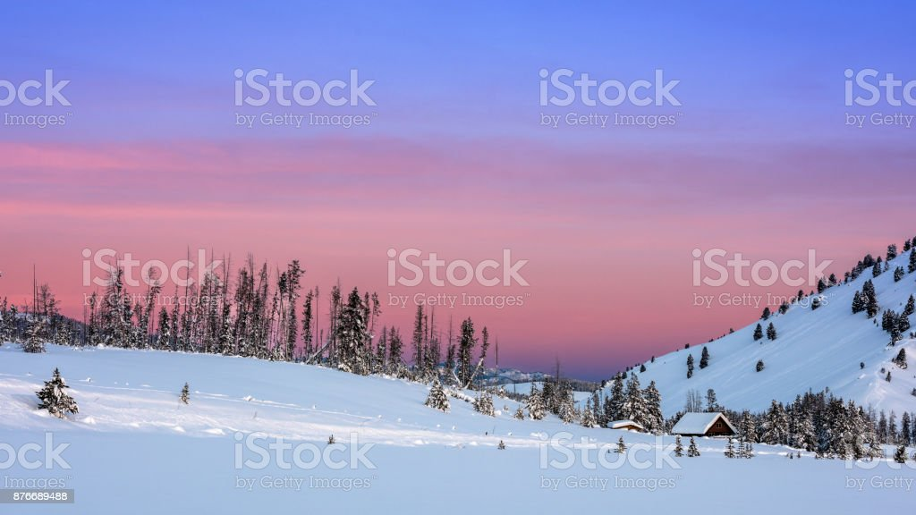 Sky colored with hues of morning over a snow covered field with cabin stock photo