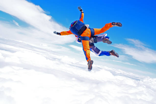 Sky diving tandem above the clouds stock photo