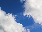 Beautiful calming fluffy white clouds in a deep blue summer sky