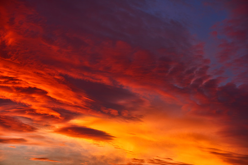 horizontal nature background of sky in fire colors, red, orange, yellow.