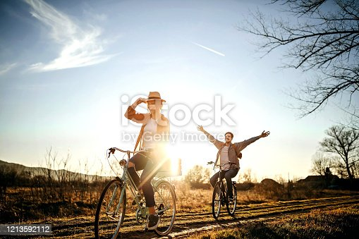 Couple driving on bicycle in nature, enjoying the sun