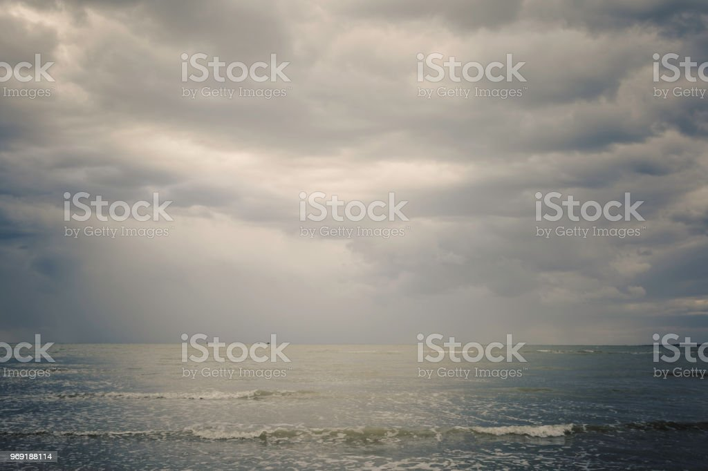 Sky with black clouds and sea, with boat on the horizon stock photo