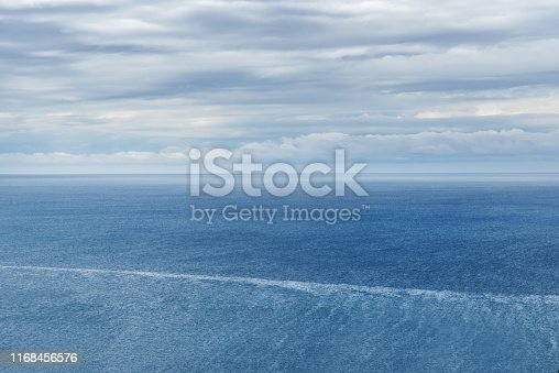 Sky with clouds and Adriatic Sea with ripples. Blue-white sea landscape