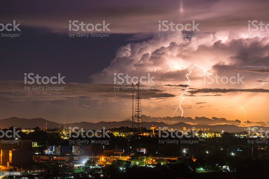 Sky with lightning striking hills behind small town stock photo