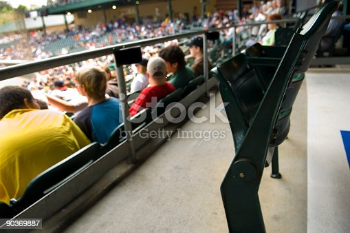 this picture is of a stadium full of people watching a sporting event. the picture is a close of the stadium seats and people sitting in the stadium seats. the picture was taken at the sporting event or outdoor music concert. the lighting is natural sunlight.