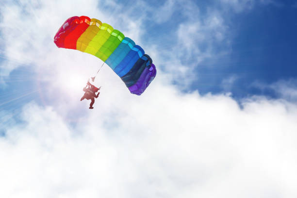 Skydiver flying on a parachute rainbow colors in the sun, against the sky. Skydiver flying on a parachute rainbow colors in the sun, against the sky. Illustration. parachuting stock pictures, royalty-free photos & images