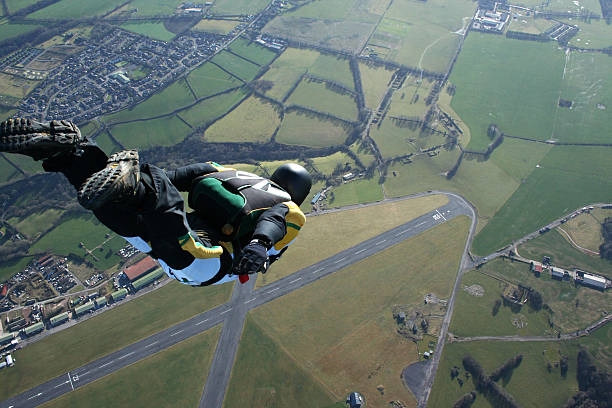skydiver free falling above countryside - daredevil stock pictures, royalty-free photos & images