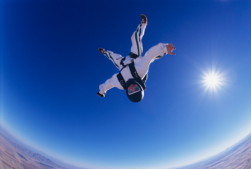 Skydiver free falling upside down portrait view from below