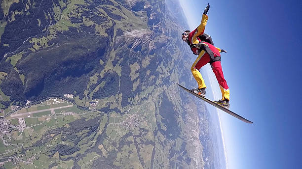 skydiver in freefall, on snowboard over mtns - 스카이 다이빙 뉴스 사진 이미지