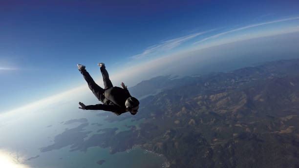 Skydiver jump over the sea and mountains stock photo