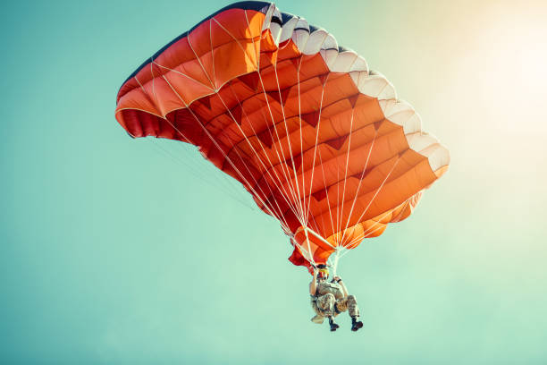 Skydiver On Colorful Parachute In Sunny Clear Sky. stock photo