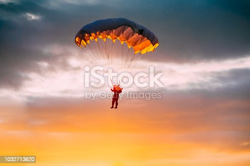Skydiver On Parachute In Sunny Clear Sky At Sunset Or Sunrise Time. Active Hobbies. Parachutist Paratrooper In Colorful Dawn Sky