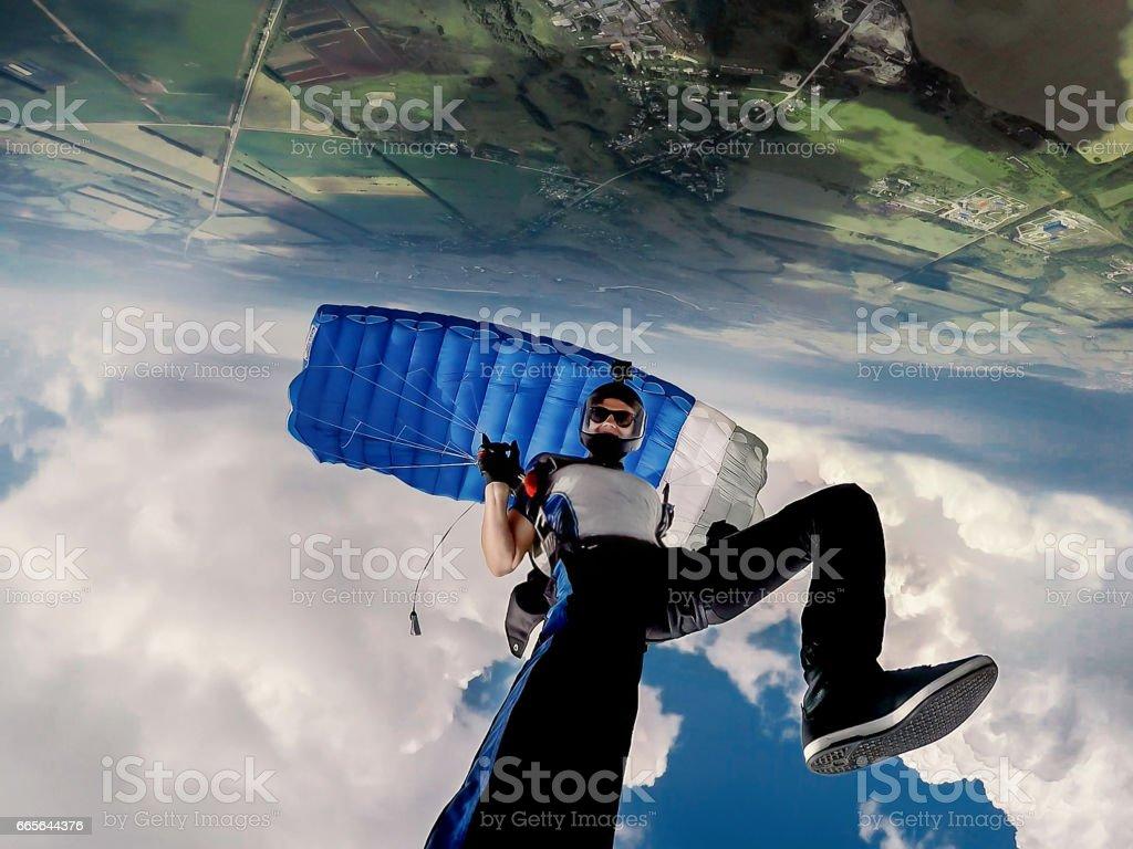 Skydiver self portrait under the blue parachute stock photo