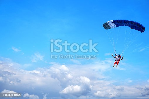 istock Skydiver with a dark blue canopy on the background a blue sky ab 1163011864