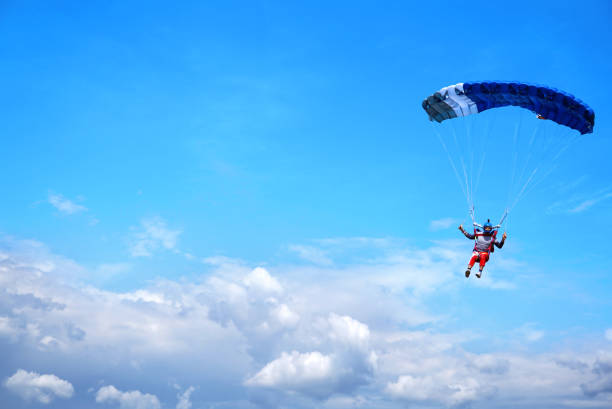Skydiver with a dark blue canopy on the background a blue sky ab Skydiver with a blue canopy of a parachute on the background a blue sky and clouds, close-up. Skydiver under parachute above the stormy clouds parachuting stock pictures, royalty-free photos & images