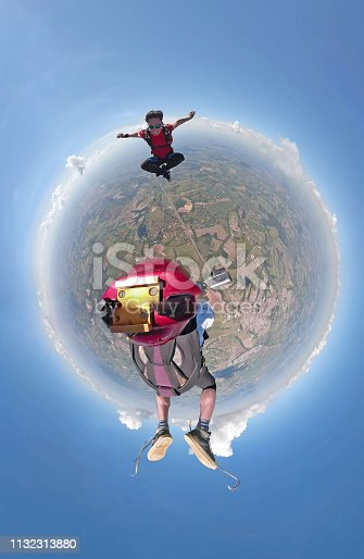 istock Skydivers having fun small planet view 1132313880