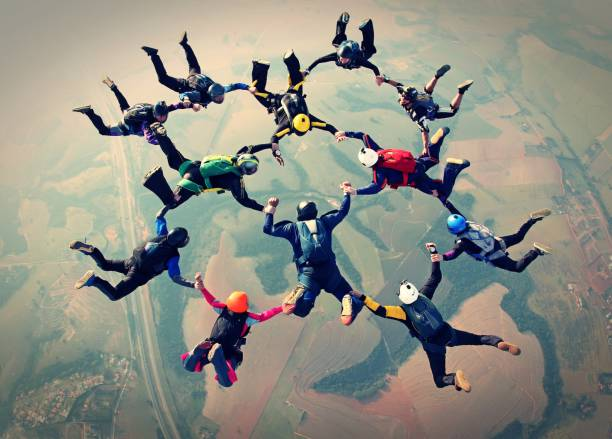 Skydivers team work photo effect Skydivers formation parachuting stock pictures, royalty-free photos & images