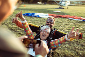 Close up of a excited senior woman taking a picture after her first tandem skydive