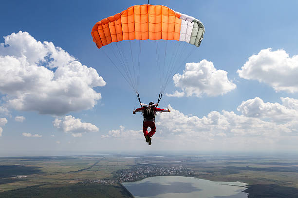 Skydiving photo. Piloting the parachute in the clouds. parachuting stock pictures, royalty-free photos & images