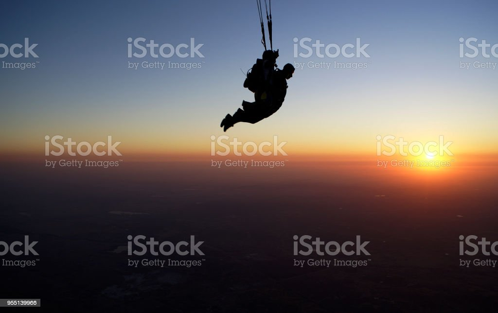 Skydiving tandem at the sunset stock photo