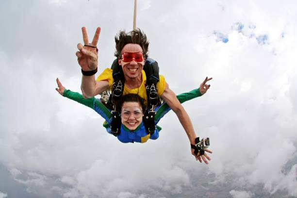 Skydiving tandem happiness on a cloudy day Skydiving tandem peace and love sign parachuting stock pictures, royalty-free photos & images