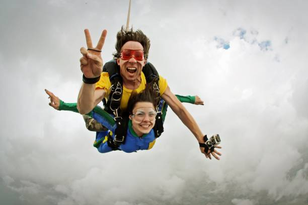 Skydiving tandem happiness on a cloudy day stock photo