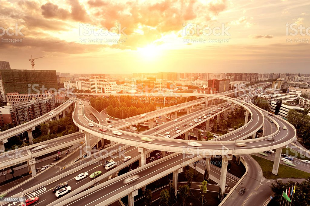 skyline and traffic trails on highway intersection stock photo