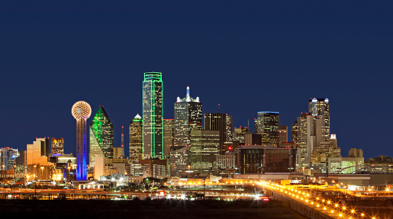 Wide-angle shot of Dallas, Texas business district showcasing skyscrapers glowing and lights glimmering at night.