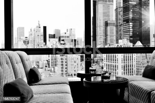 Window inside a bar lounge. There are two sofa and two small coffee tables. On the tables there are flowers in a bowl. Out of the window there is a panoramic view of Upper Midtown Manhattan, NYC.
